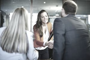 young lady greeting two people who will be doing a job interview.