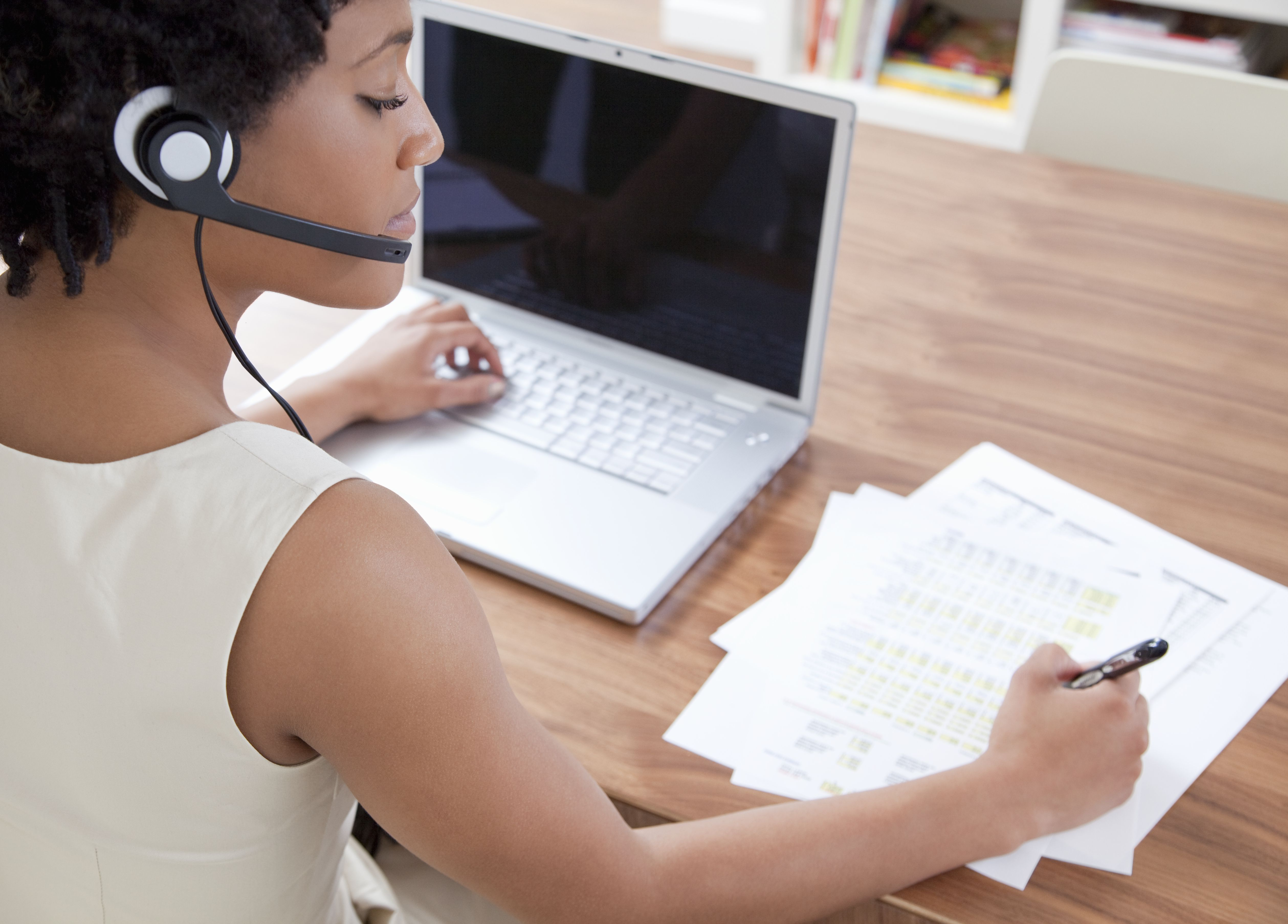 Businesswoman using headset and laptop computer