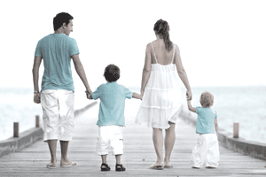Parents and two children walking hand-in-hand on a pier