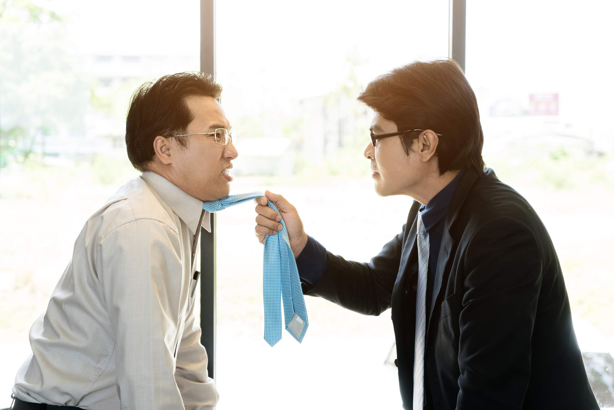 Angry man holding his coworker by the tie.