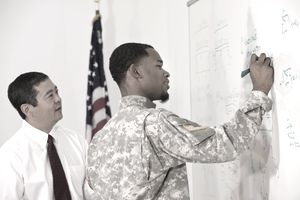 Businessman watching soldier writing on whiteboard