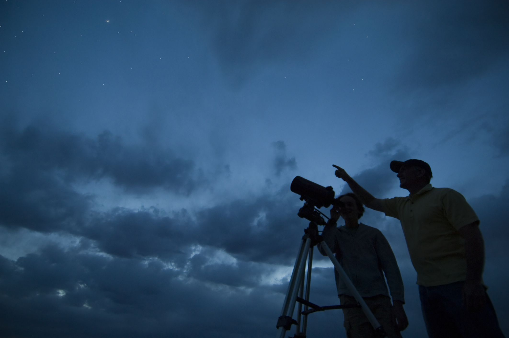 Astronomers looking through telescope
