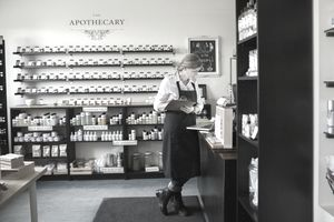 Apothecary shop owner taking inventory with clipboard