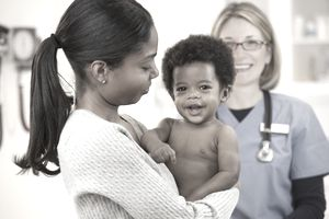 Doctor examining baby boy who is covered via mom's health insurance benefits.