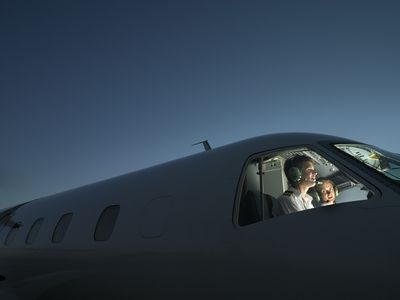 Two pilots in illuminated cockpit of plane, smiling