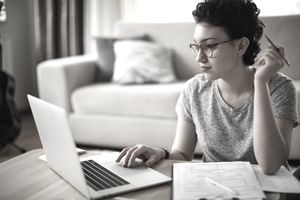 Young woman writing a resignation letter on a laptop.