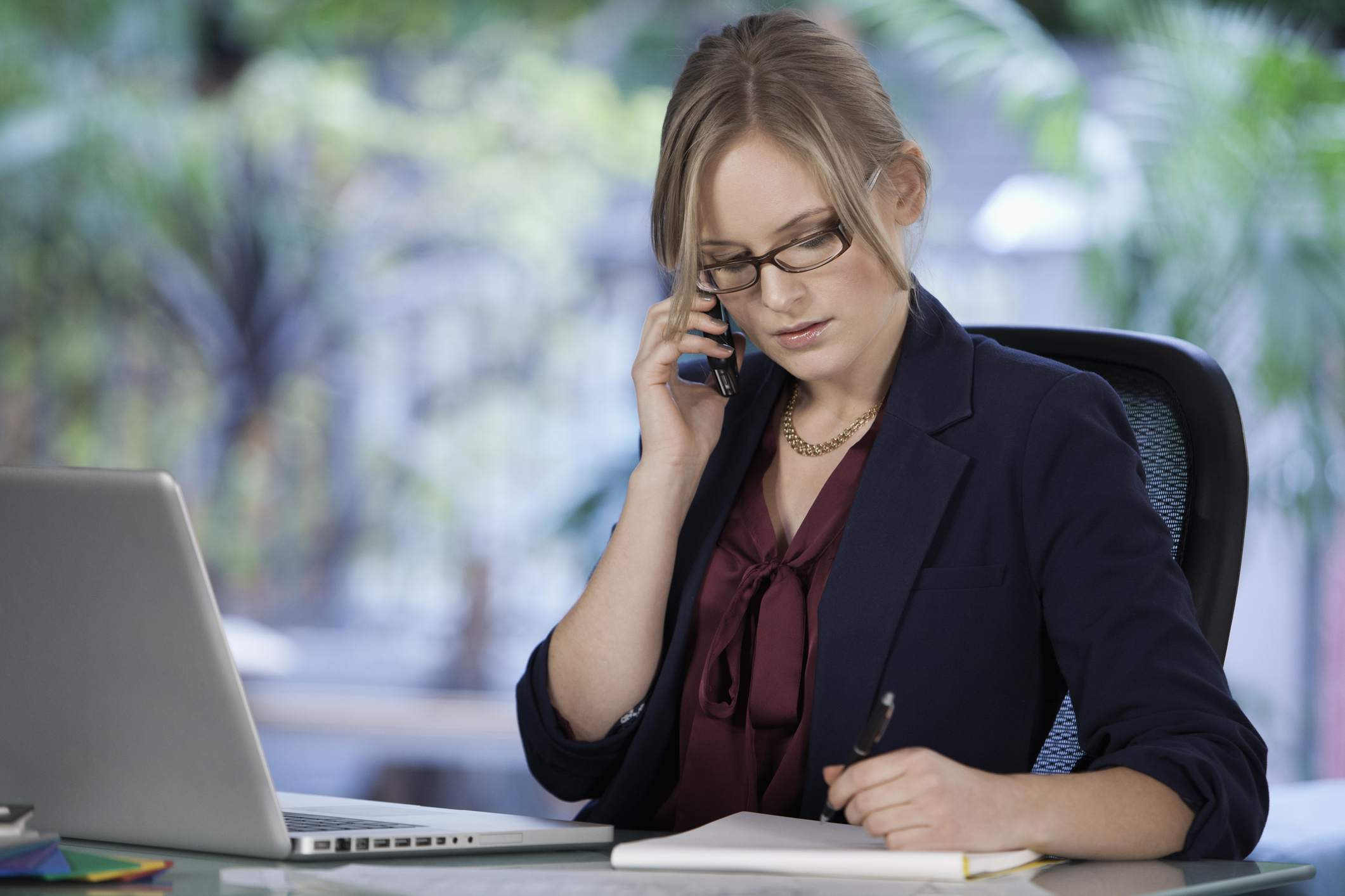 Caucasian businesswoman talking on cell phone and working