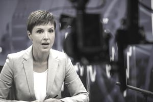 Female journalist in front of a camera.