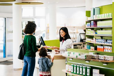Small Family Being Served By Chemist At Local Pharmacy