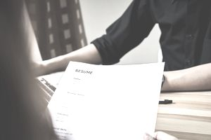Woman handing resume over during interview