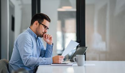 Serious pensive thoughtful young businessman or entrepreneur in modern contemporary office looking at and working with laptop and paper documents making serious and important business decision