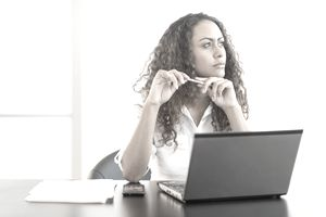 Woman sitting at her desk looking pensive