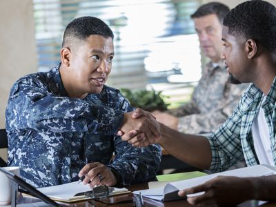 soldier meeting with young man at military recruitment event