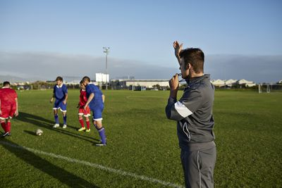 a soccer coach on the field with young soccer players