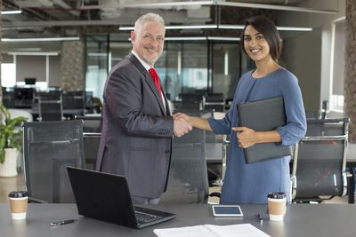 A businessman and a businesswoman shaking hands to close a deal