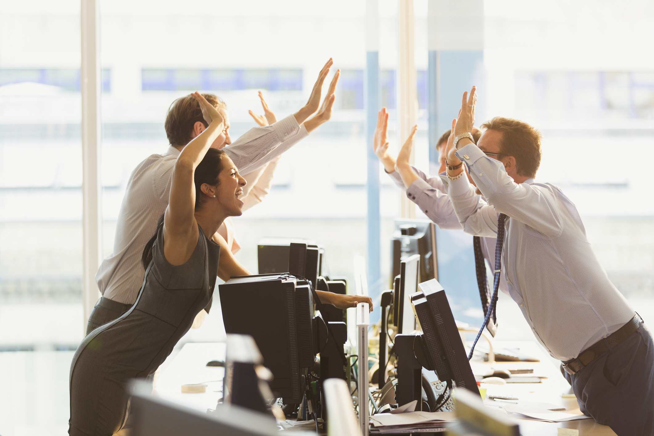 Exuberant business people high-fiving over computers in office