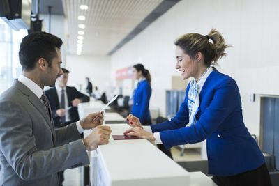 Ticketing agent taking materials from a customer at the airport