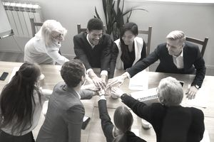 Multiracial business people put hands together at group team meeting