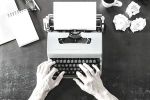 person sitting at typewriter