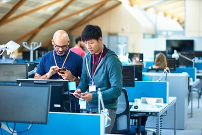 two employees utilizing their information technology skills working on fixing a tech issue at a computer