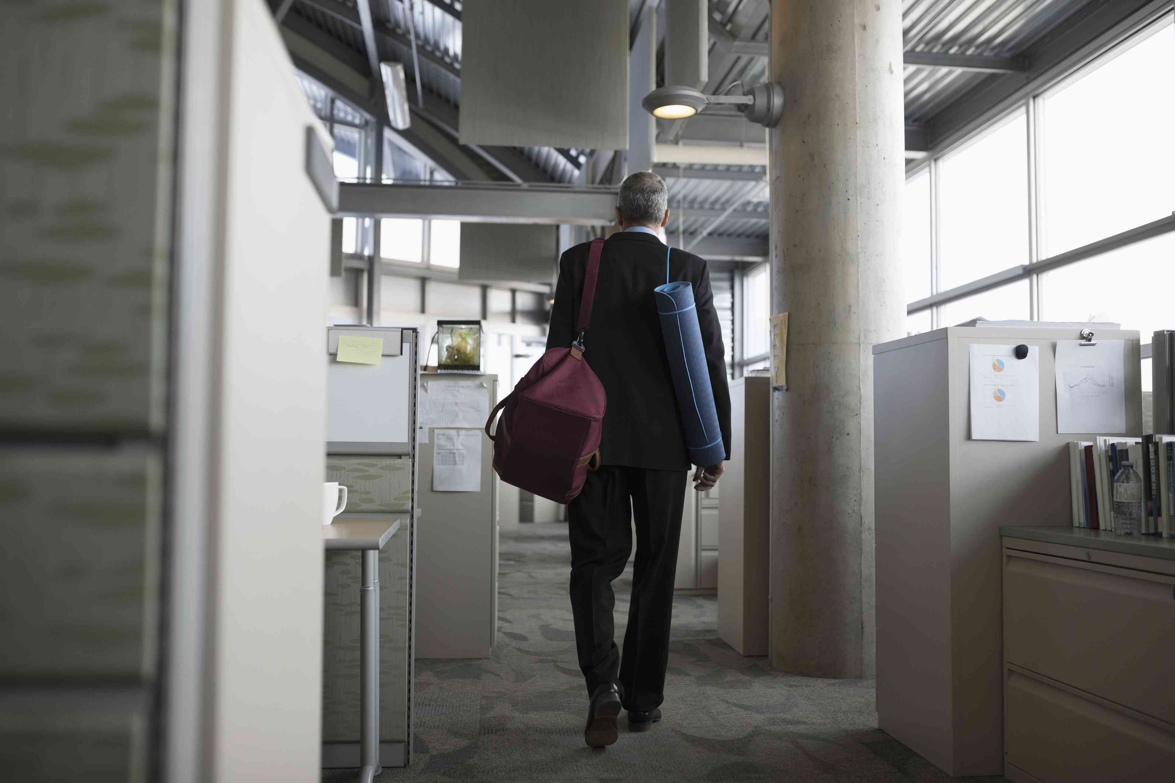 Businessman leaving office with gym bag and yoga mat