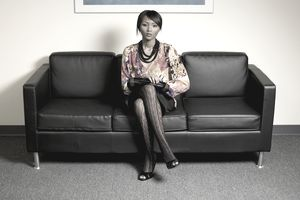 Nicely dressed woman sitting on sofa waiting.
