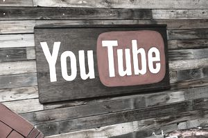 YouTube logo on a wooden wall