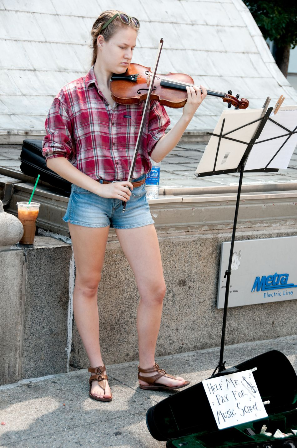 A woman busking with a violin