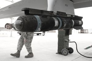 Air Force Aircraft Armament System technician check munitions under wing of a jet.