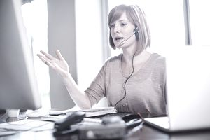 Woman at desk wearing a headset