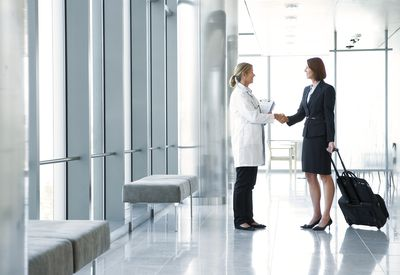 Pharmaceutical rep with product samples shaking the hand of a doctor before a sales presentation