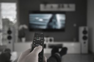 hand holding remote pointed at television screen