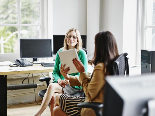 Two businesswomen discussing project on digital tablet at office workstation