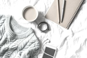 Blue knitted sweater, coffee with milk, notebook, headphones, phone on bed, top view. Women clothing. Flat lay