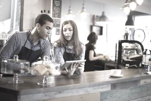 Young employees looking at iPad in cafe