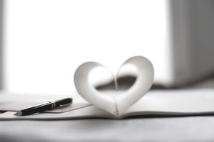 Pen and pages of notebook forming a heart-shape