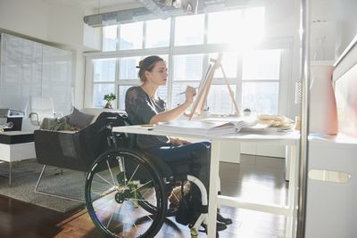 woman in wheelchair painting on easel