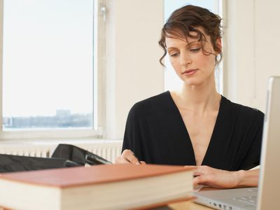 a woman working at a desk in front of an open laptop