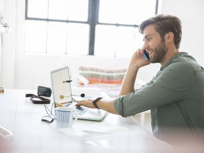 Many working at computer and talking on phone