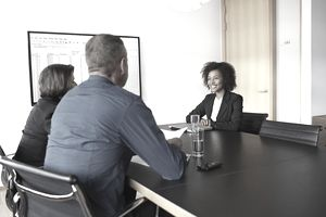 A woman sitting across the table from two people as she interviews for a job in sales.