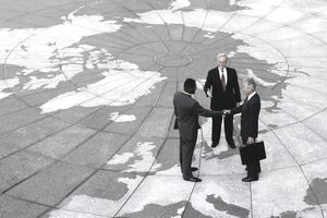 Lawyers meeting outside a courthouse on tile plaza showing the continents