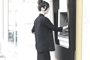 Business woman withdrawing money from ATM