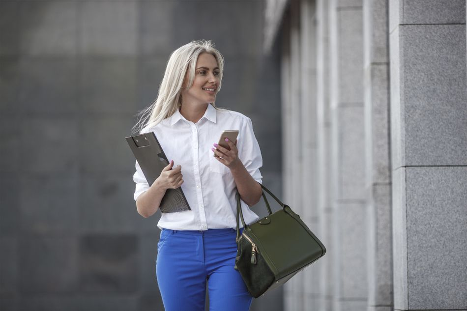 business woman walking with clipboard and smartphone in hand and carrying a leather purse on her arm