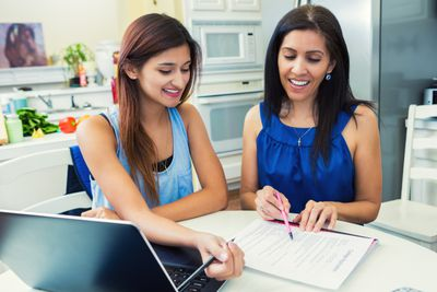 Mother helping daughter fill out College Applications