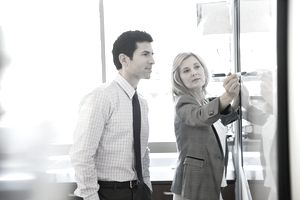 Businesswoman writing on a whiteboard while businessman observes
