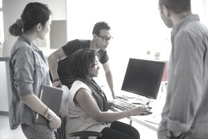 Cross-functional team of software developers working with office staff on usability of a new computer app.