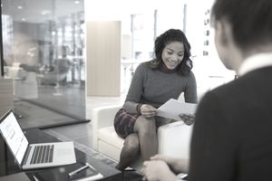 Businesswomen reviewing resume in office lobby
