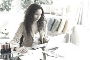 A Businesswoman Sitting at Desk Using a Laptop