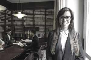 Portrait of female lawyer standing in boardroom with colleagues in background