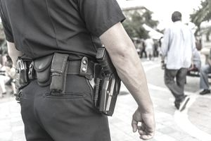A close up of a police officer's at an event showing his duty belt with handcuffs and firearm.